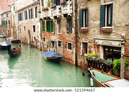 16 October 2016 , Venice ,Italy. Gondoleer sailing on the canals in a cloudy day . #521394667