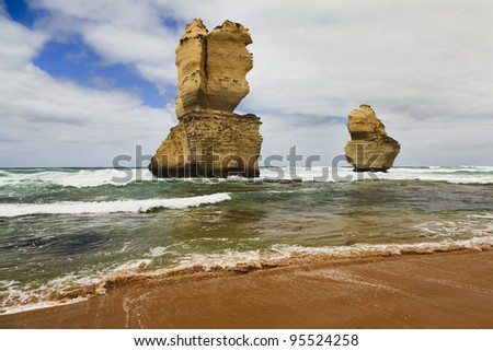2 of 12 apostles - giant and beautiful nature park in Australia along Great Ocean Road majestic day time view from sandy beach with surfs and blue sky