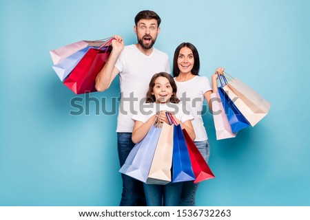 50% off! Real bargain concept. Portrait of excited three people mom dad schoolkid shop center hold bags scream wow omg wear white t-shirt denim jeans isolated over blue color background