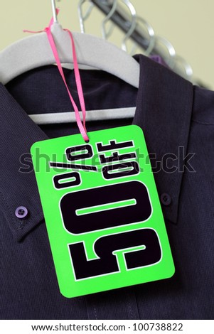 50% off sign hanging on clothes hanger in front of a row of shirts
