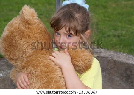 Offended child embraces her toy bear. The girl looks tragic and firmly presses for a toy.