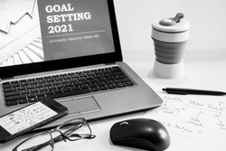 2021 Office desk and presentation devices with notebook, mouse computer, paper note for Goal Setting, eye glasses and tumblr. Concept for business plan on Black and white photo