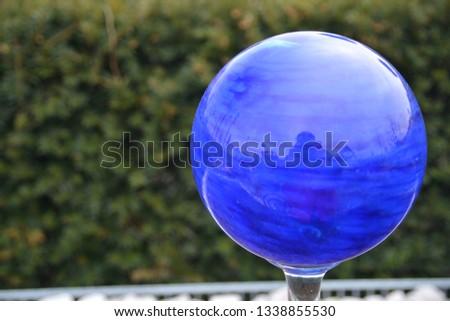 Ogrodowa ozdoba. Niebieska szklana kula. Rozmyte zielone tło. Po lewej miejsce na tekst. Zdjęcie poziome.  Zdjęcia stock ©