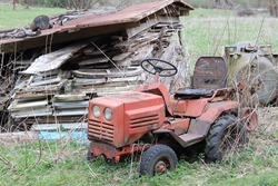 Old and small tractor in the old yard