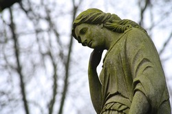 Old antique grave sculptures with moss.  Sculptures of sad angels in the cemetery.