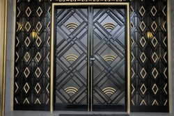 Old black and gold art-deco door. Frontage on street.