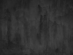Old black painted metal wall. Grunge texture with cracked paint. Gray background with drips of paint. Rough dirty texture. Monochrome.
