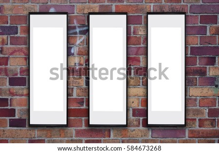 Old brick wall with three empty vertical long  poster frames. Mock up.