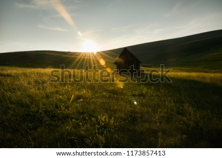 Old cabin in meadow sunset. #1173857413