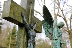 Old Crucifix in a graveyard, Jesus on the cross. Green bronze angel statue in the background.