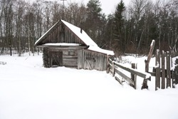 Old dilapidated wooden abandoned house on the edge of the forest in winter among the snow