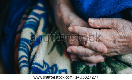 old hands grandmother in a colorful background. close up, overhead, copy space. wrinkled skin of aged person. aging process.