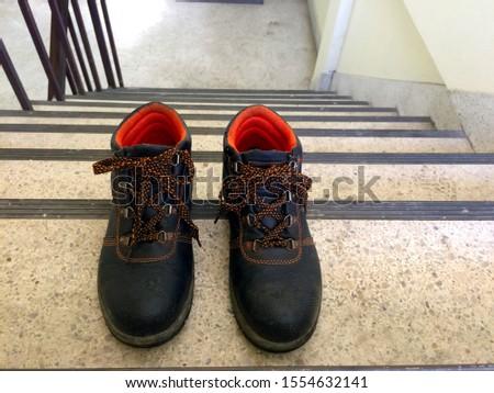 Old pair of dark brown steel shoes Shoelace black, orange pattern Put it on the cement floor #1554632141