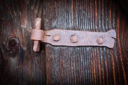 old rusty door hinge on wooden door surface