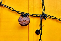 Old rusty padlock and chain on metal door.