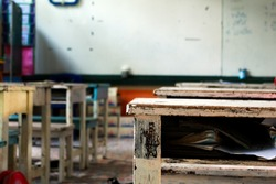 old school desk with other desks and white board on background in classroom , at the rural school development education concept.