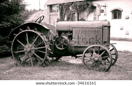 old tractor with iron wheels is thrown on a roadside