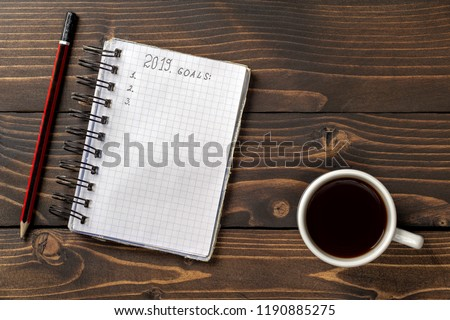 On a brown wooden table, a cup of coffee, a pencil and an old notebook with plans for the next year.