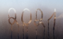 2021 on misted glass. The concept of the outgoing year.