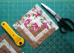 On the mat for patchwork sewing there are scissors, a knife for patchwork, a ruler, a patchwork napkin