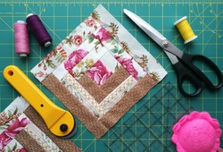 On the mat for patchwork sewing there are scissors, a knife for patchwork, a ruler, a patchwork napkin and threads