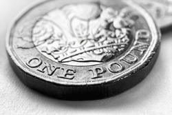 1 one British pound coin. Black and white background or wallpaper about money and economy of Great Britain. Brexit. Focus is on denomination of coin and name of currency of UK. Macro