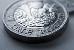 1 one British pound coin close-up. Grey tinted background about economy, business, finance or banking. Backdrop from Britain's money. Coins of England. Classic gray color. Macro
