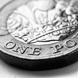 1 one British pound coin. Dramatic black and white square illustration about money and economy of Great Britain. Brexit. Focus is on denomination of coin and name of currency of UK. Macro