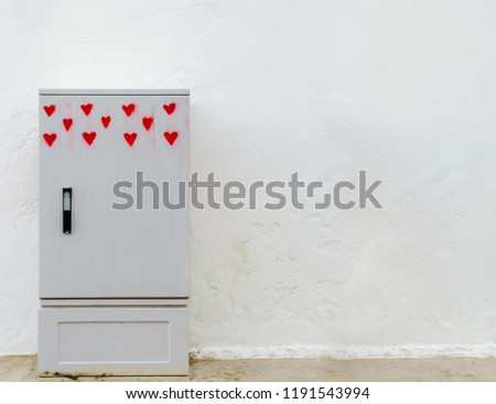 One gray junction box painted with eleven red hearts in front of a white, structured wall as copy space or wallpaper #1191543994