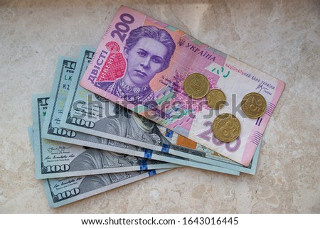 one hundred dollar bills and hryvnia bill coins top view