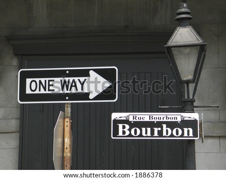 'one way' sign pointing to Bourbon St. sign