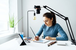 Online content creator vlogger. A young women blogger with glasses removes the content for the blog, training courses. The concept of online learning to watercolor