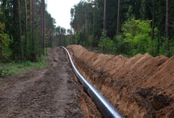 Сonstructing pipelines that transport oil, natural gas, petroleum products and industrial gases. A dug trench in the ground for the installation of industrial gas and crude pipes.