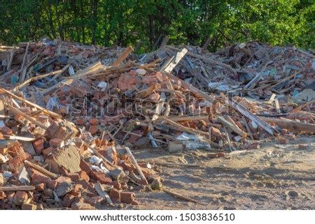 Сonstruction garbage, debris and waste rubble in a remote green area. Nature and soil pollution concept