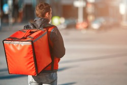 Сontactless food delivery to customers home. Delivery service worker with thermal backpack quick delivering food at doorstep in quarantine from restaurant, supermarket or cafe . Online ordering food