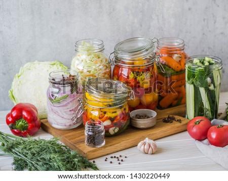 Сooking pickled vegetables. Salting various vegetables in glass jars for long-term storage. Preserves vegetables in glass jars.  Variety fermented green vegetables on wood board