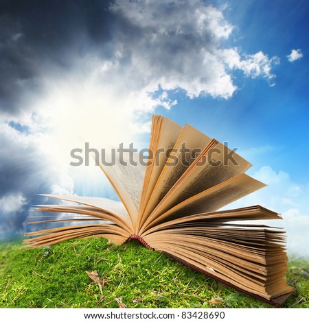 open book on moss/ ground, sky as a background - stock photo