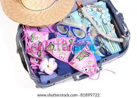Open suitcase with bikini and sunglasses and beach items