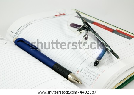 Opened diary planer with pen on pure white background