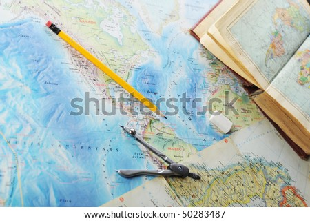 opened old atlas book on  map and pencil - stock photo