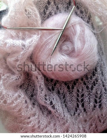 Openwork mohair pattern on silk. Background for knitting. Warm, cozy scarf. Made by hand with knitting addi on the fishing line. A ball of gently pink wool close-up.