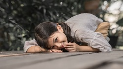 7 or 8 years old Asian school kid image.Girl happy and relax on her holidays in oriental nature garden. Earth tone portait of Asian kid.