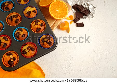 orange curd muffins with chocolate lie in a baking dish on a wooden tray on a white background with piaces of chocolate and oranges. Top view                             Stock fotó ©