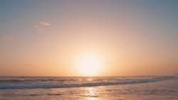 Orange sundown on the beach over the sea nature background landscape with big yellow sun, blue sky and amazing sea. Sun sundown or sunset on evening Atlantic ocean beach landscape.