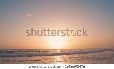 Photo of   Orange sundown on the beach over the sea nature background landscape with big yellow sun, blue sky and amazing sea. Sun sundown or sunset on evening Atlantic ocean beach landscape.