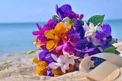 Orchids Bridal bouquet on the beach with a blue sky.
