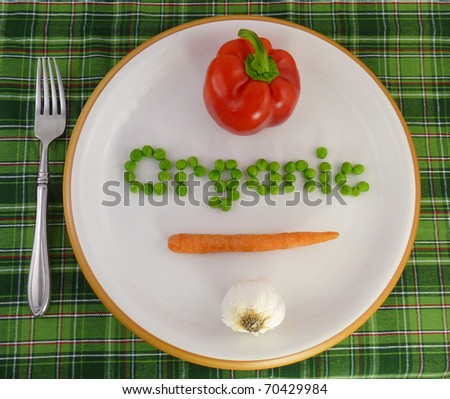 """Organic"" spelled out in vegetables on a white plate with a green plaid table cloth and a fork"
