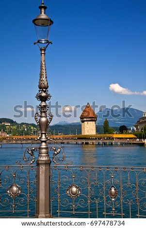 /Ornate railing/Ornate railing (with lamp) on river of Lucerne, Switzerland. Overlooking central walking bridge. #697478734