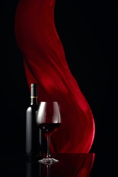 Вottle and glass of red wine on a black reflective background. Red cloth flutters in the background. Copy space.