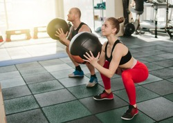 Сouple functional training. Sporty man and fit woman do exercise with medicine ball in gym